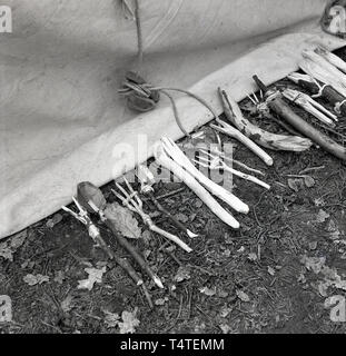 1960s, historical, hand-made wooden cutlery - spoons and forks made from twigs - made by adventure scouts laid outside a tent. - Stock Image