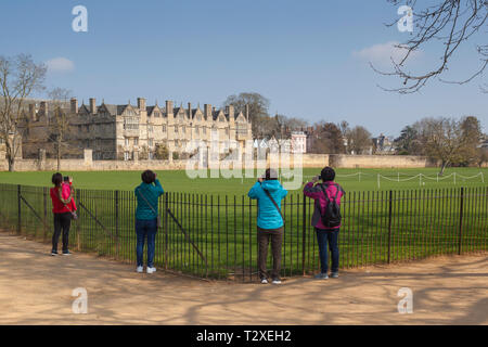 Tourists photograph Merton College Oxford across Merton Field from Christ Church Meadows - Stock Image
