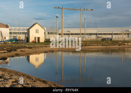 Staniforth Cottage, a grade II listed building on Calshot spit reflected in the Solent. It was a coastguard building, converted into military use. - Stock Image