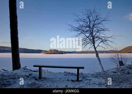 Wooden bench standing at the shore of an ice covered lake. - Stock Image