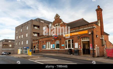 London, England, UK - June 1, 2019: New build apartment buildings rise behind Southbury London Overground railway station in the North London suburbs. - Stock Image
