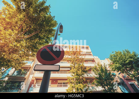 View from bottom of 'no parking' road sign with blank frame for your text placed on street lantern, facade - Stock Image