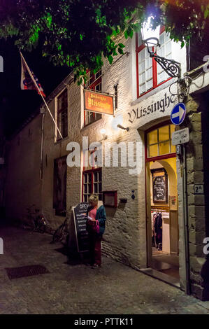 A woman reading a map outside Café Vlissinghe, at night, Bruges, (Brugge), Belgium - Stock Image