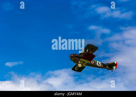Flying biplane Spad S XIII replica from first world war between the clouds. - Stock Image