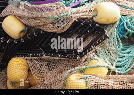 A pile of sea fishing gear, ready for use by the local fishing industry, on a harbour, including bouys, ropes and netting - Stock Image