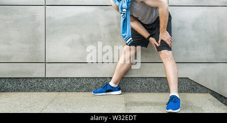 Knee ache and sport injury. Young man holding his painful knee and feeling bad. sport and healthcare lifestyle concept. cropped and standing on gray w - Stock Image