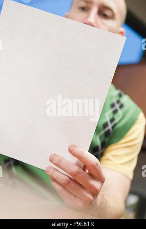 View of a Caucasian man going over paperwork in his office. - Stock Image