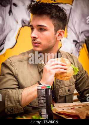 Young man eating a hamburger holding it with his hands - Stock Image