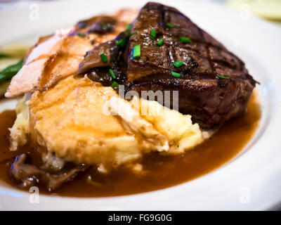 Steak, potatoes, and gravy on a white plate - Stock Image