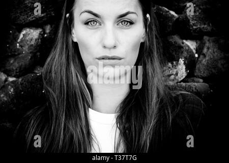 Black and white beautiful caucasian young woman portrait with clear blue eyes and serious expression - Stock Image