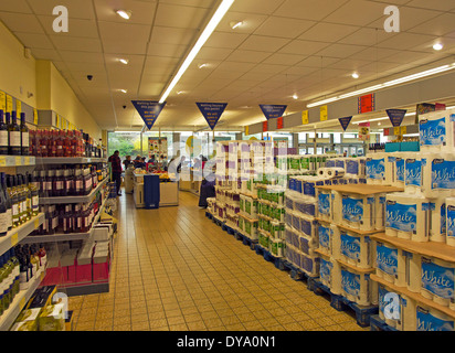 pallets of toilet paper and kitchen towels and shelves of reasonably priced wine towards the check out area - Stock Image
