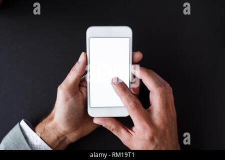 A top view of male hands hodling smartphone on a desk. Copy space. - Stock Image