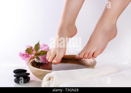 Woman legs and feet with french nails polish in spa studio with wooden bowl with water and decoration pink flower and black rock. Pedicure and health - Stock Image