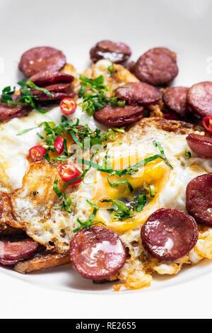 spicy chorizo sausage and eggs spanish huevos rotos with fries tapas snack - Stock Image