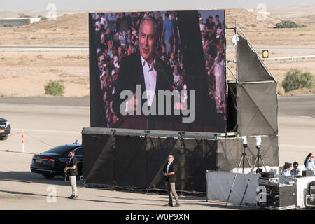 Hazerim Air Base, Israel. 27th June, 2019. Security men stand guard as Israeli Prime Minister BENJAMIN NETANYAHU is projected on a screen giving an address at a graduation ceremony honoring Air Force pilots and navigators following their successful completion of one of the most competitive and rigorous training processes in the IDF at Hazerim Air Base in the Negev Desert. Credit: Nir Alon/Alamy Live News. - Stock Image