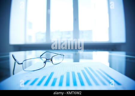 Image of eyeglasses and document on workplace - Stock Image