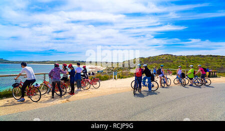 Tourists with bicycles parked beside Salmon Bay on Rottnest Island - Stock Image