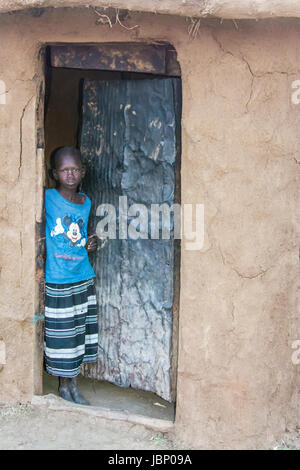 Maasai child standing in the doorway of a mud hut, wearing a Mickey Mouse T-shirt, in a village near the Masai Mara, - Stock Image