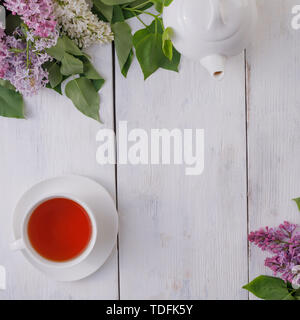 Tea set and flower decor against a background of white-painted wooden boards. Vintage background with lilac flowers and a place under the text. View f - Stock Image
