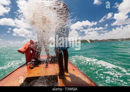 Fishing in a jangada - seaworth sailing raft used by fishermen of northeastern Brazil. Ponta Negra beach, Natal city, Rio Grande do Norte State. Morro do Careca, Natal landmark, in background. - Stock Image