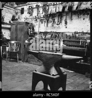 Interior of a workshop, 1966-1974. The interior of a workshop with a blacksmith's anvil in the foreground. The location of this site is unidentified, but it is probably in East Lancashire or West Yorkshire. - Stock Image