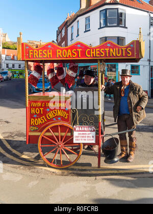 Hot Chestnut vendors in traditional dress selling nuts roasted on their hand cart in Whitby North Yorkshire - Stock Image