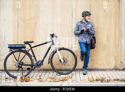 Active senior man with electrobike standing outdoors in town, leaning against a concrete wall and using smartphone. Copy space. - Stock Image