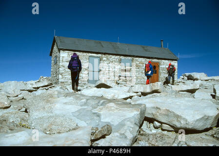 Hikers approach the storm shelter on the summit of Mount Whitney in the Sierra Nevada, California - Stock Image