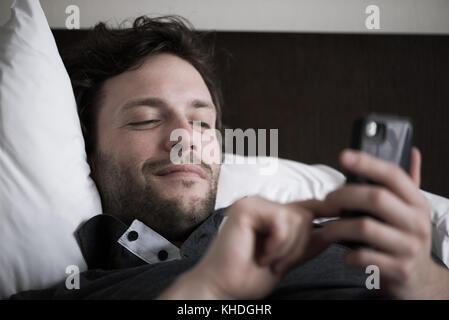 Man reclining in bed using smart phone - Stock Image