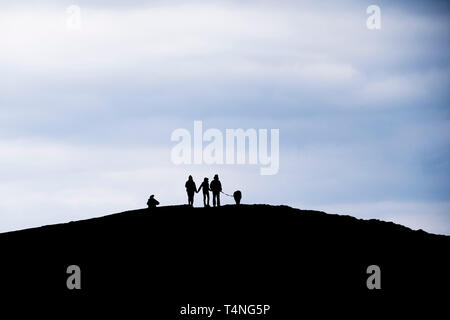 The silhouette of a family walking their dog on highest point of Pentire Point East in Newquay in Cornwall. - Stock Image