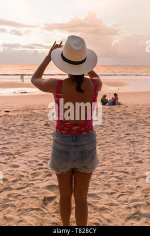 Phuket, Thailand - 13th June 2017. Tourist girl taking photograph of sunset, Bang Tao beach. There are many days that provide stunning sunsets. - Stock Image