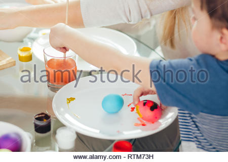 Preschooler boy helping his mother to paint out the boiled white eggs for Easter Holiday Celebration, focus on hand, dipping the paintbrush in a glass - Stock Image