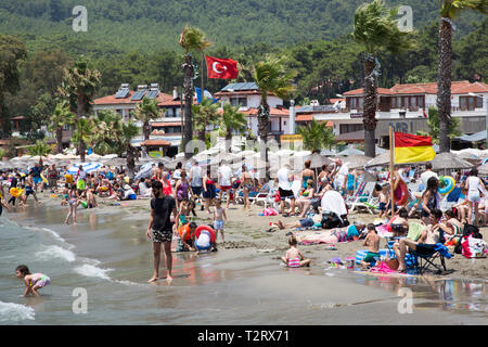 Tourists and locals enjoying the sun on the public beach, Akyaka, Mugla province, Turkey. - Stock Image