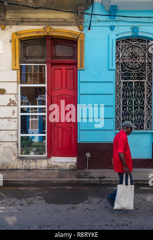 Cuban Man with carrier bag walking along brightly coloured street in Havana Cuba. The red door matches the colour of his shirt. - Stock Image