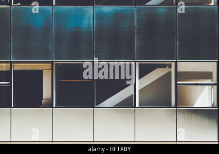 Blue and white modern facade of contemporary building with several rows of metal and glass plates in Barcelona on - Stock Image