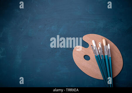 Artist paint brushes and palette with copy space, flat lay - Stock Image