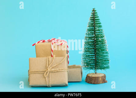 Pile of gift boxes wrapped in craft paper tied with twine red white ribbon Christmas tree on mint blue background. New Year corporate presents shoppin - Stock Image