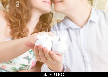 Crop couple with tiny footwear on hands - Stock Image