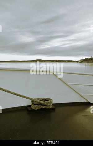 Detail of a ship lying moored in an ice covered harbor bay. Monochrome photograph,tones sepia and blue. - Stock Image