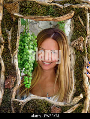 Lady with grape in frame - Stock Image