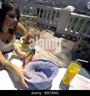 Mother and toddler relaxing at a pavement cafe in Mijas Pueblo, Costa del Sol, Andalucia, Spain - Stock Image