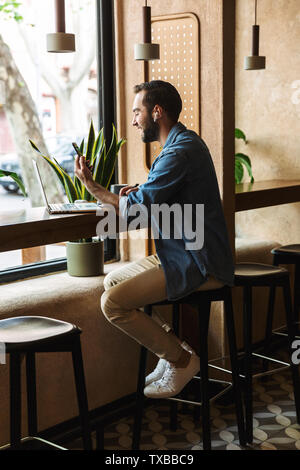 Photo of unshaven caucasian man wearing denim shirt using earpod and cellphone with laptop while working in cafe indoors - Stock Image