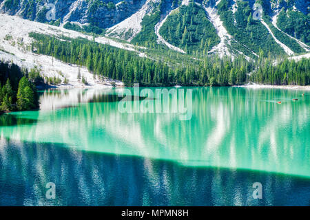 beautiful colors of Braies lake in summer season with sunny light, shadow and mountain Croda del Becco in background, Dolomites - Italy - Stock Image