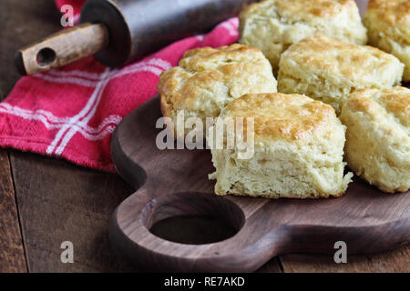 Freshly baked buttermilk southern biscuits or scones from scratch over cutting board. - Stock Image