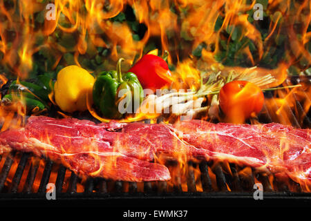 Stock image of steak and vegetables on a barbecue grill with flames - Stock Image