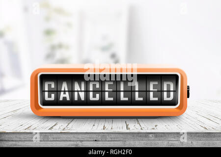 Cancelled message on a retro alarm clock in a bright room with a weathered wooden table - Stock Image
