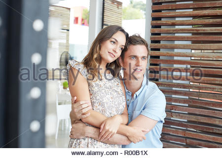 Young couple embracing whilst sitting - Stock Image