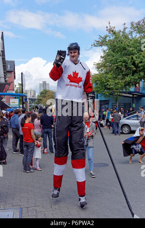 Vancouver, Canada.1st July, 2018. A man dressed as a Canadian hockey player on stilts waves at onlookers in the annual Canada Day Parade on Granville Island, Vancouver, British Columbia. This year Canada Day celebrates the country's 151st birthday. Credit: John Mitchell/Alamy Live News - Stock Image