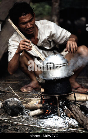 An indigenous, ethnic Lahu man cooking rice over an open fire in his village in northern Thailand. Rice plays a - Stock Image