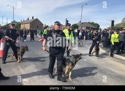 Police separate demonstrators on Derby Road, Bootle, Merseyside, after Tommy Robinson leaves following an election campaign event. - Stock Image